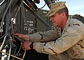 US Navy 090217-N-1120L-005 Information Systems Technician 1st Class Alan Decker, assigned to Naval Mobile Construction Battalion (NMCB) 7, inserts a cord into the transmitter dish of a Ruggedized Deployable Satellite Communicat.jpg