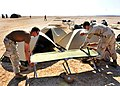 US Navy 091216-N-9187B-002 Seabees assigned to Naval Mobile Construction Battalion (NMCB) 3, assemble a cot for an overnight stay before a 15-kilometer run through the Grand Bara Desert in Djibouti.jpg