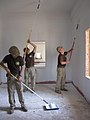 US Navy 100524-N-0827C-001 Sailors assigned to Naval Mobile Construction Battalion (NMCB) 11, based in Gulfport, Miss., paint the ceiling of the Hope Center engineering site.jpg