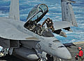 US Navy 101014-N-9811S-049 A Sailor assigned to the Red Rippers of Strike Fighter Squadron (VFA) 11 enters the cockpit of an F-A-18F Super Hornet t.jpg