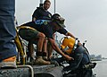 US Navy 110612-N-OS584-155 Navy Diver 2nd Class Nick Johnson is helped onto a pontoon after completing a welding and salvage dive during Cooperatio.jpg