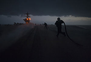 US Navy 120121-N-DR144-126 Sailors run to install slot seals in a catapult track.jpg