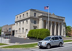 A light tan stone building with a classical colonnade and pediment on the front with an American flag flying against a blue sky from a flagpole out front. Parked on the street in front is a light blue Honda minivan.