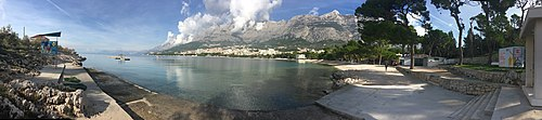 Panoramic view of Makarska view from the edge of its longest beach compromised by concrete and advertisting