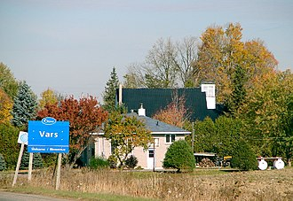 Vars, Ontario - Sign seen coming in to Vars, with some properties in the background.