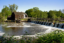 A large river flowing from a spillway; a mill in the background