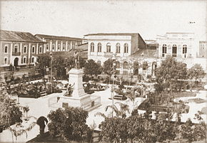 A photograph overlooking a large city plaza containing low trees and walkways in the center of which stands a sculpture on a high plinth