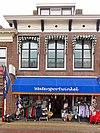 foto van Woonhuis met verdieping met zesruitsvensters en met versierde kroonlijst onder dwarskap met hoekschoorstenen