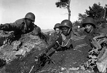 Four soldiers sitting in a foxhole, one soldier is pointing a machine gun towards the camera while another is pointing out targets