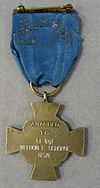 Back of a bronze cross-shaped medal hanging from a blue ribbon