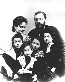 A middle-aged, bearded man, a younger woman and four children