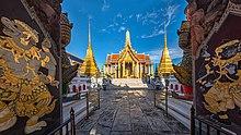 Eine thailändische Tempelanlage mit mehreren kunstvollen Gebäuden und vielen Besuchern