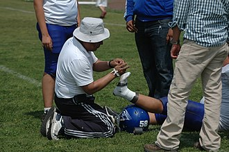 Sports injury - Player getting ankle taped at an American football game in Mexico