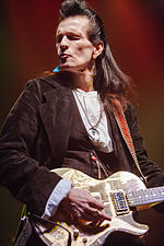 The head and torso of a middle-aged man. He has long, dark hair. He is wearing a dark jacket, a light top, and several items of jewellry, including large earrings. He is playing an electric guitar.
