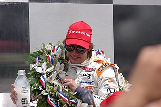 Indianapolis 500 traditions - 2011 Indianapolis 500 winner Dan Wheldon celebrating with a bottle of milk in victory lane.