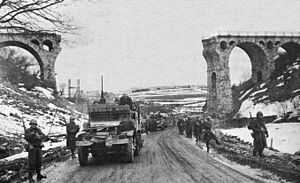 26th Infantry Regiment (United States) - The 1st Battalion, 26th Infantry passing through the railway viaduct north of Bütgenbach, Belgium, on the Monschauer St. (N647) towards Bütgenbach. The railway viaduct was part of the line running from Losheim/Eifel (Germany) to Trois-Ponts, Belgium, and had been blown up by the retreating German troops.