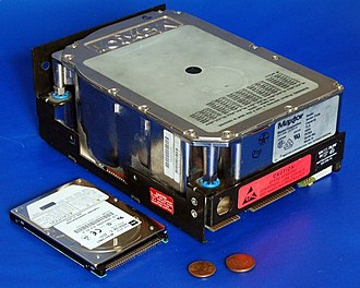 Maxtor - An early Maxtor hard drive (right) with a modern laptop hard drive and currency for size comparison