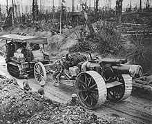 A large field gun and limber being towed along a sunken road through a battle-scarred forest by a Holt tractor. The gun has large fabricated steel-spoked wheels, with a wide tread to cope with mud.