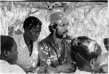 Medico latinoamericano dalla pelle chiara con cuffia in Guinea Bassau tra quattro nativi dalla pelle nera.
