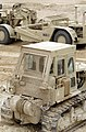 A bulldozer and a scraper stand ready for use by members of Naval Mobile Construction Battalion 5 as they prepare the area for camp construction during Operation Desert Storm. Exact - DPLA - 8c230c47c110cadfe31d361f3ee4bf3c.jpeg