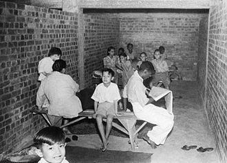 Bombing of Singapore (1941) - Civilians hiding in an air raid shelter at Tiong Bahru Estate during a Japanese bombing raid in December 1941.
