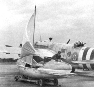 Vickers Warwick - A rigged airborne lifeboat in front of a Warwick with D-Day identification stripes