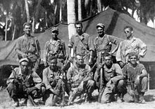 Black-and-white image of ten men in two rows, the top row standing and the bottom row crouching, are all facing the camera. They are wearing military attire and are holding rifles.
