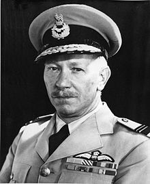 Head-and-shoulders portrait of a caucasian man in light-coloured uniform with peaked cap and pilot's wings on left-breast pocket