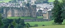 Un gran castillo, con una zanja y árboles enfrente.