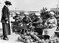 An officer of the Womens Royal Naval Service (WRNS) supervising the wiring together of glass floats on an anti-submarine mine net during the First World War. Q19640.jpg