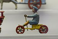 Antique tin toy boy on wagon (25920010410).jpg