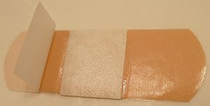 Release liner - An adhesive bandage with a release liner partially removed.