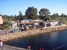 Colour photo showing the reconstruction of the ancient port of Palos de la frontera: transportation barrels, low buildings bordered by a covered gallery, a chariot at the very edge of the water awaiting the arrival of a boat.