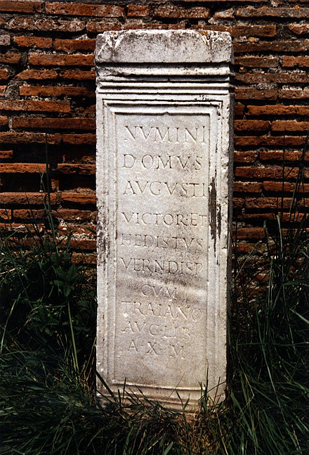 "Dedicatory inscription ( CIL 14.04319) to the ""numen of the House of the Augustus"", from Ostia Antica Bauinschrift, CIL XIV, 04319, Forum der Korporationen.jpg"