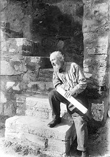 Uma fotografia em preto e branco do arquiteto Bernard Maybeck, datada de 1919. Na fotografia, Maybeck está olhando para o lado esquerdo da moldura e descansando em um degrau, ligeiramente inclinado para a direita com o pé direito puxado para cima. passo, o pé esquerdo no chão e a mão esquerda segurando um grande papel enrolado (possivelmente uma planta, indicativa de seu trabalho como arquiteto).