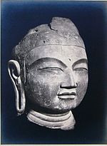 A Buddha head in three-quarter view with elongated earlobe, thick lips, narrow slit eyes and broad nose.