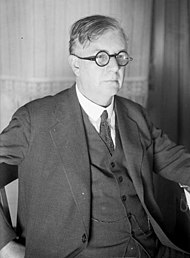 A middle-aged man in a suit, with slightly-unkempt, parted hair and small circular glasses