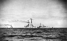 Two large warships steaming in opposite directions close together, with several other vessels are in the distance.