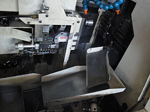 Automatic lathe - A view inside the enclosure of a CNC Swiss-style screw machine.