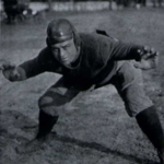 Football player in uniform, crouching with arms and legs spread