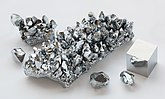 A silvery finger of chromium irregularly encrusted with diamond-like chunks of chromium of varying size. There is also a one-third sized version of the finger and three roughly hewn gem-like chunks of chromium, as well as the cube. There is a partial reflection of one of the three gem-like chunks in one of the faces of the cube.