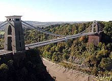 A suspension bridge spanning a river gorge with woodland in the background