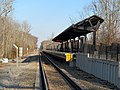 Cohasset station platform from parking lot access road, March 2014.JPG