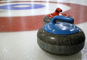 Curling stones on rink with visible pebble.jpg