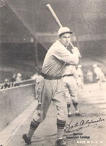 A man wearing a baseball cap and jersey poses prior to swinging his baseball bat.