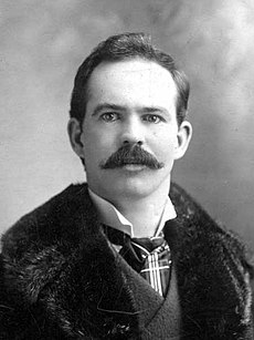 Upper body of a man with short hair and a thick moustache. He is wearing what appears to be a fur coat over a suit.