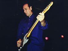 A man, wearing blue, plays an electric guitar and gazes down on the ground.