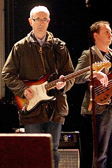 Dik Evans holding a guitar in front of a microphone stand