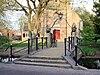 foto van Kerkring. Voor de toren der Hervormde Kerk een boogbrug met balustraden over het water van de Kerkring. Voorts een toegangshek met hardstenen palen
