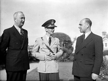 a black and white photograph of two older men alongside a young man in uniform